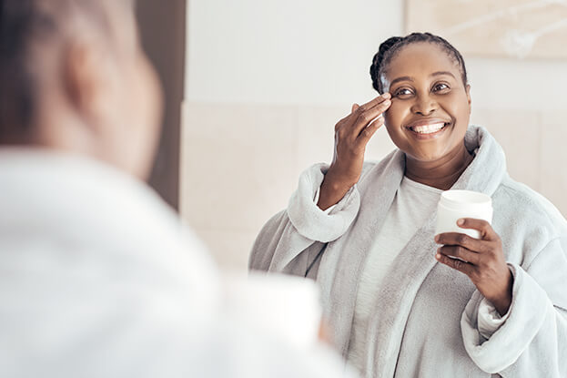Smiling happy woman applying moisturizer in bathroom