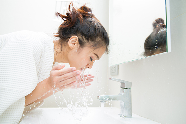 Woman washing face at the sink