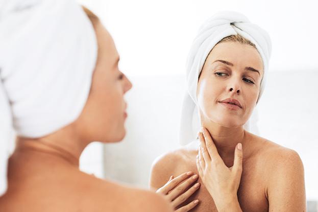 Woman applying serum on neck