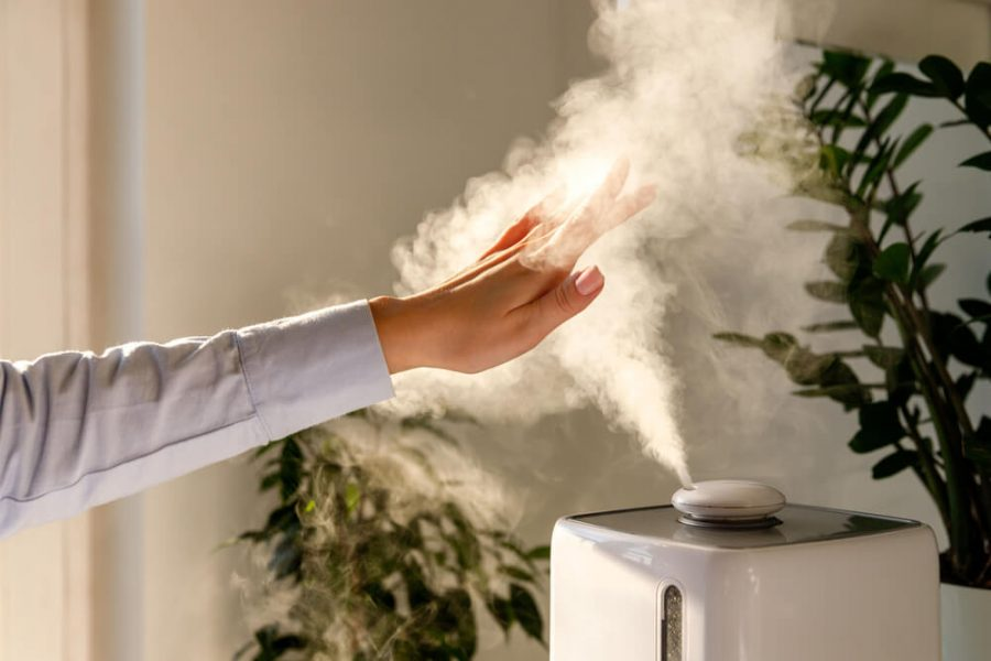 Hand touching steam from humidifier