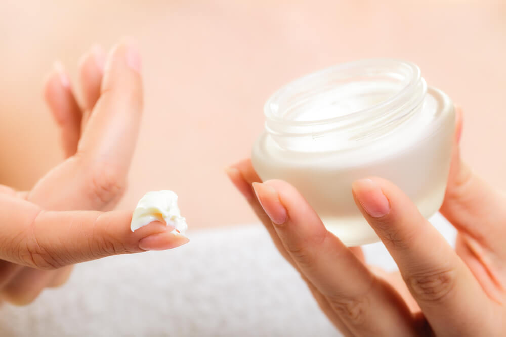 Hand with skin cream on finger