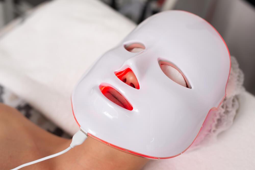 Woman using LED mask