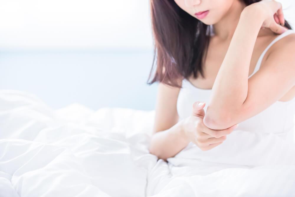 Woman moisturizing elbow